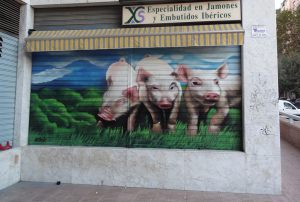 Mural-graffiti-de-cerdos-en-persiana-de-charcuteria